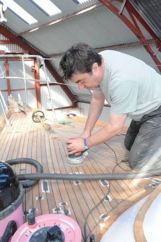 Barry Lovell sanding a teak deck
